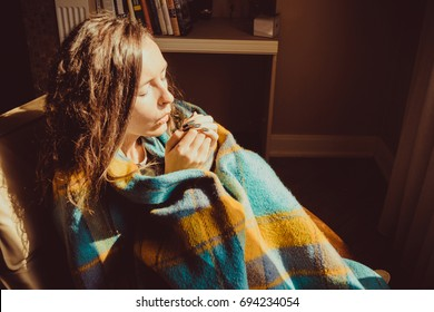 Winter cold concept. Young freezing woman in comfortable chair warming frozen hands wrapped in warm fluffy woollen plaid blanket. Natural light. Warm atmosphere. Heating season. Cosy home