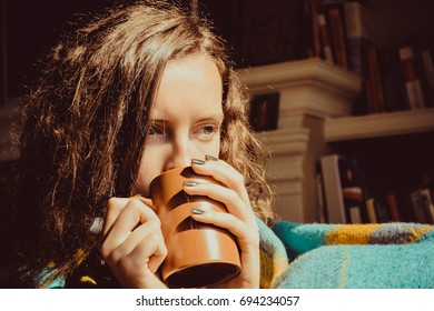 Winter cold sickness concept. Young freezing pensive woman with mug tea wrapped in warm plaid blanket. Natural light. Warm atmosphere. Cup Hot Beverage. Heating season. Close up female face. Cosy home