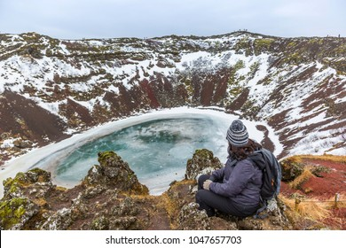 The winter colours of beautiful Kerio, or Kerid crater in western Iceland. Red volcanic rock, green mossy slopes and a circle of breaking ice in a turquoise lake