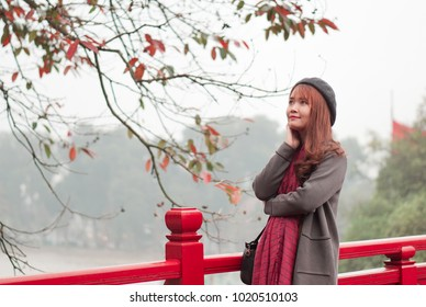 Winter is coming to a beautiful girl is standing on the red bridge named The Huc in Hanoi, Vietnam