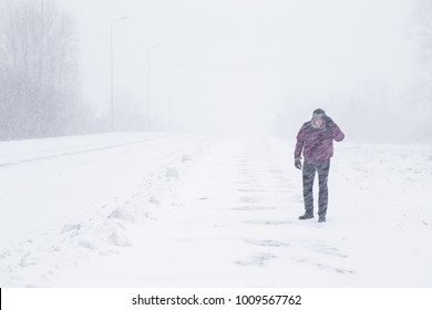 Winter is coming by snow. Poor visibility in heavy snow storm on path. Man slowly and hard walking in dangerous weather day. Cataclysm of nature. City people life in blizzard concept.