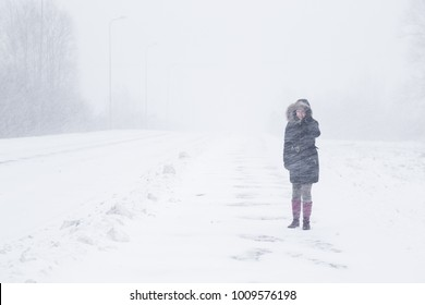 Winter is coming by snow. Poor visibility in heavy snow storm on path. Woman slowly and hard walking in dangerous weather day. Cataclysm of nature. City people life in blizzard concept.