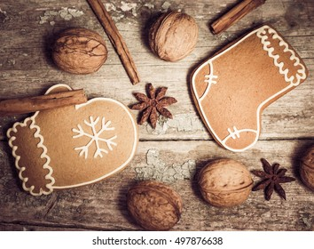 Winter composition with gingerbread cookies, spices and walnuts on an old wooden background. Christmas theme. Top view