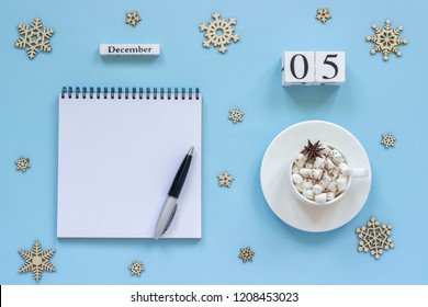 Winter composition. Wooden calendar December 5 Cup of cocoa with marshmallow and star anise, empty open notepad with pen and snowflake on blue background. Top view Flat lay Mock up Concept