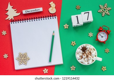 Winter composition. Wooden calendar December 17th Cup of cocoa with marshmallow, empty open notepad with pencil, snowflake, alarm clock on red and green background. Top view Flat lay Mockup