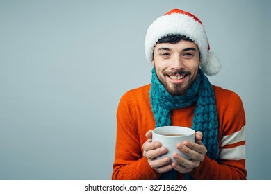 Winter concept - Christmas holiday. A man in the red sweater wearing a Santa Claus hat holding a large cup of tea. Isolated on a gray-blue background