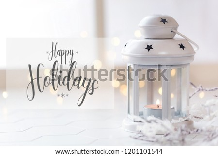 Winter concept - a Christmas lantern with a lit candle with a window and festive lights at the background. Shallow depth of field with copy space for your greetings