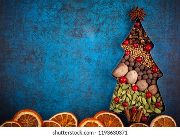 Winter concept with Christmas spices in shape of Christmas tree on blue background. Top view with copy space.