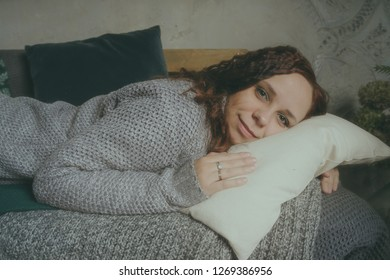 Winter Concept. Cute young girl in a gray knitted sweater. Beautiful woman is relaxing in a white bedroom. Beautiful women in clothes are waking up in the morning. Woman wearing a sweater