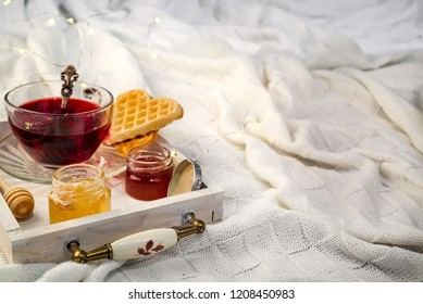 Winter concept with knitted blanket and hot tea with waffer, jam, honey on wooden tray on te bed. Copy space