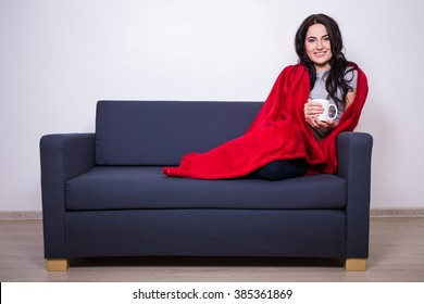 winter concept - young woman sitting on sofa with mug of tea wrapped in warm red blanket