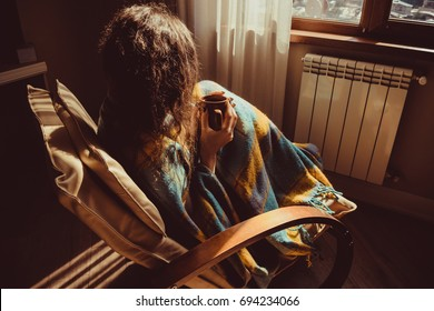 Winter concept. Young woman sitting in comfortable modern chair near radiator with mug of tea wrapped in warm plaid blanket. Natural light. Warm atmosphere. Cup Hot Beverage. Heating season. Cosy home