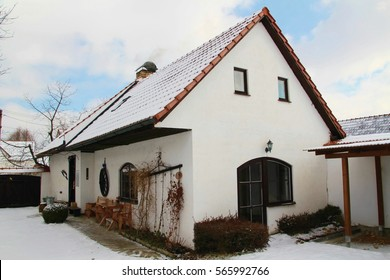 Winter cottage under layer of snow, side perspective, blue cloudy sky, new roof tiling