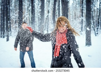 Winter couple having fun playing snowball fight