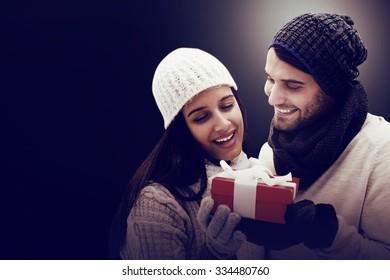 Winter couple holding gift on dark background