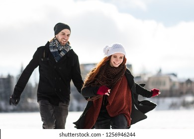 Winter couple running over the snow in mountains