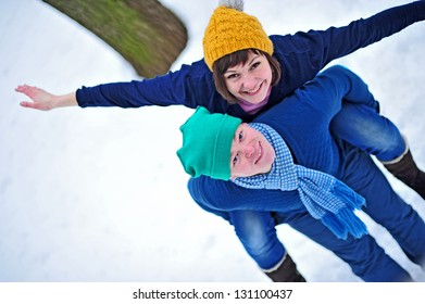 Winter couple in snow smiling happy. Beautiful love young couple