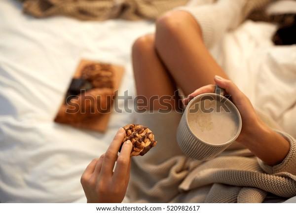 冬、コシネス、レジャー、人々のコンセプト – コーヒー、カカオ、クッキーを入れた若い女性の接写