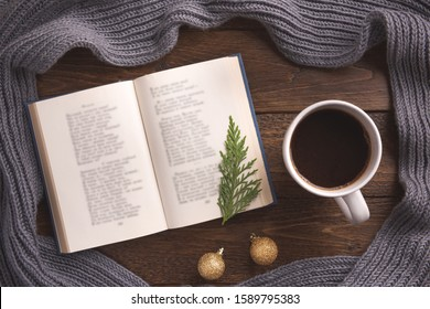 Winter, cozy composition. Warm scarf, book and cup of coffee, on wooden background. Flat lay, top view, copy space.