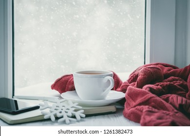 Winter cozy hot chocolate in front of window, snow, sweater. Lazy weekend, love, comfort