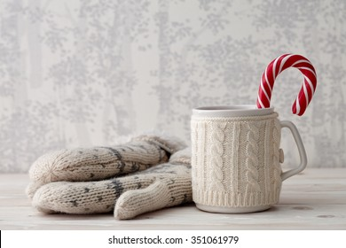A winter cup of hot drink with a candy cane and mittens on a light textured background