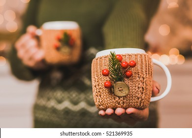 Winter cups. Mugs of hot tea or coffee or cocoa  in knitted vintage cup holders with christmas decorations in hands of woman with beautiful festive red manicure. Woman proposing one cup into camera