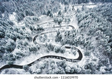 Winter curved winding road in the forest covered in snow