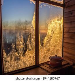 Winter dawn in frozen window. Frozen window winter sunrise - Shutterstock ID 1944183967