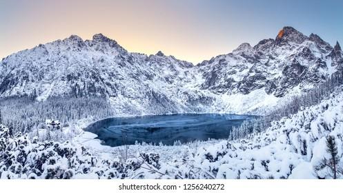 Winter dawn in mountains. Beautiful winter landscape with mountain lake and snowy hills. Morskie oko lake. Lake in tatra mountains in winter at dawn. Poland, Zakopane. - Shutterstock ID 1256240272