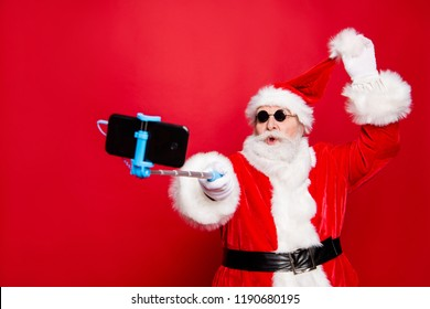 Winter December noel christmastime eve wish trendy stylish aged mature senior Santa headwear tradition costume white beard take selfie picture on front camera smartphone isolated on red background
