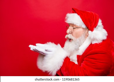 Winter December sale discount black friday. Profile side view aged Santa in costume blow on open palms hand near face pouted lips isolated on shine red background with copy space for text