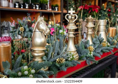 Winter decor. Beautiful arrangement of golden chess pieces, natural spruce branches, golden cones for luxury Christmas New Year holidays interior decor in greek flower boutique.