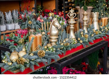 Winter decor. Beautiful arrangement of golden chess pieces, natural spruce branches, golden cones, candles for luxury Christmas New Year holidays interior decor in greek flower boutique.