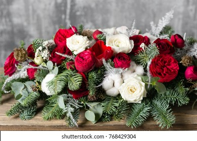 Winter decor. The composition of the branches Nobilis and fresh flowers. Work florist in shop. For decorating a family dinner