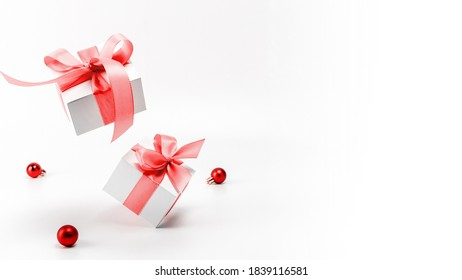 Winter design. White gifts with red ribbon and New Year balls in xmas decoration on white background for greeting card. Copy space. Winter holidays, New Year.