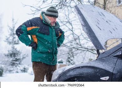 Winter difficulties with the car, problems due to bad weather conditions. Unrest on the road en route. The man is trying to get out of the problem and trouble situation with the car