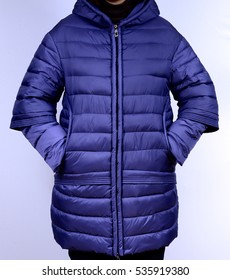 Winter down jacket isolated on a grey background. Fashionable purple coat on model without face. Outerwear.
