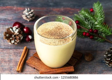 Winter drink, Eggnog, traditional Christmas cocktail, with rum, eggs, milk, heavy cream, sugar, nutmeg and cinnamon. Wooden table