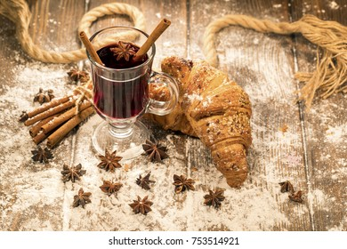 Winter drink. Hot mulled wine and croissants on a table