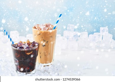 Winter drink iced coffee in a glass and ice coffee with cream in a tall glass surrounded by ice on white marble table over blue background with snow. Selective focus, copy space for text. Horizontal.