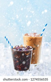 Winter drink iced coffee in a glass and ice coffee with cream in a tall glass surrounded by ice on white marble table over blue background with snow. Selective focus, copy space for text.