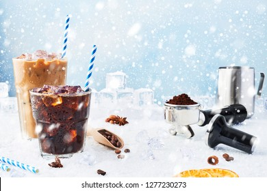 Winter drink iced coffee in a glass and ice coffee with cream in a tall glass surrounded by ice, coffee beans, portafilter, tamper, milk jug and various spices on snow over blue background. Copy space