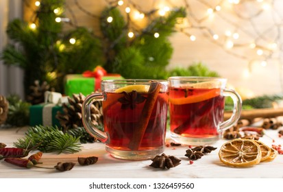 Winter drink with spices on festive new year background. Mulled wine or Christmas tea with cinnamon, red pepper, anise and lemon on rustic woden background