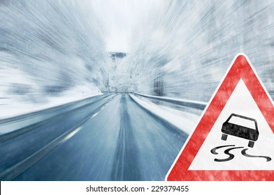 Winter Driving - Caution - Mountain road with snowfall and traffic sign