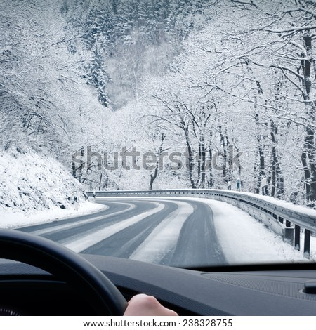 Winter Driving - Curvy Snowy Country Road - Curvy snowy country road leading through a mountain landscape.
