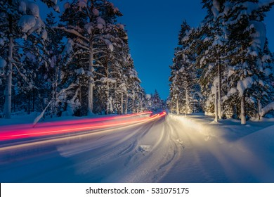 Winter Driving - Lights of car and winter road in dark night forest, long exposure