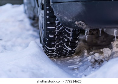 Winter driving problems, snow and ice. Extreme winter road. Frozen car wheel in ice and snow. Close up of car tire on the snowy road.