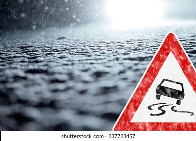 Winter Driving - Winter Road - Caution Snow - Abstract winter background with warning sign - Snow covered road at night.