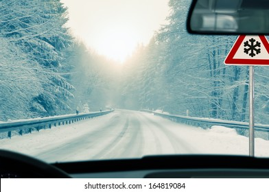 winter driving - snowy country road driving in winter - snowy country road and warning sign: risk of snow and ice