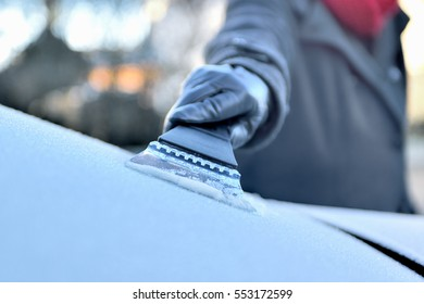 Winter Driving - Woman is scraping Ice from the frozen windows of her car